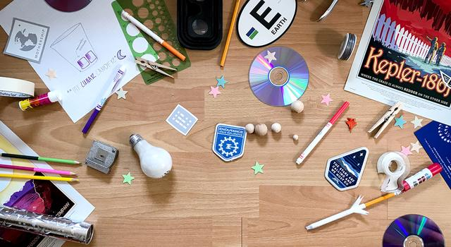 Office supplies, craft materials, space stickers and other objects strewn across a wood floor.
