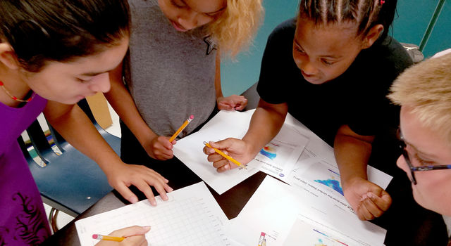 Kids surround a table full of printouts of heat maps and worksheets.