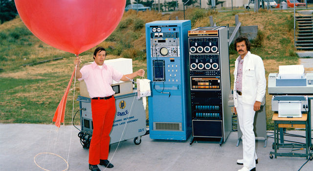 A man in bright red pants and a pink shirt holds a giant red balloon. To his left are two tall computer stations with various nobs and buttons and another man wearing an all white denim suit.