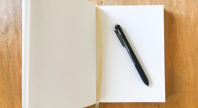 Photo of a journal and pen on a desk