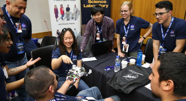 NCAS participants in navy shirts surround their mentor and point to a small robot they built