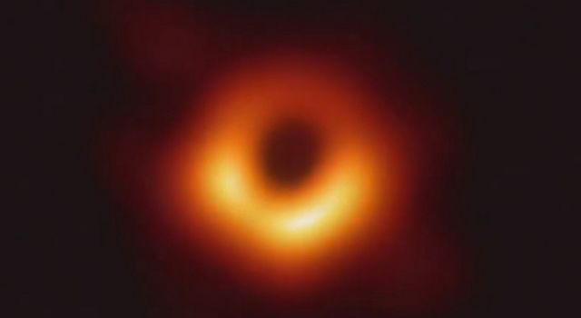In this historic first image of a black hole, an orange glowing donut-shaped light can be seen against the black backdrop of space. At the center of the light is a black hole.