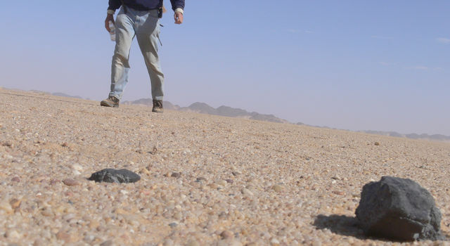 The dark object in the bottom right of this image is a meteorite from the small asteroid 2008 TC3, which landed in Sudan's Nubian Desert in 2008.