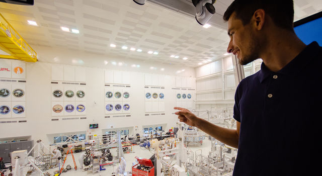 Adrien Dias-Ribiero stands in the gallery above the clean room at JPL and points down at engineers in building the Mars 2020 rover.