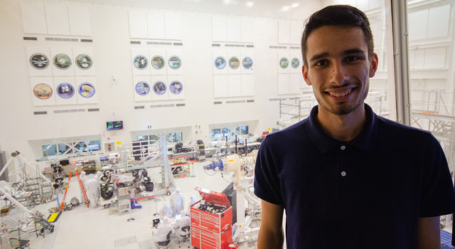 Adrien Dias-Ribiero poses for a photo in the gallery above the clean room at JPL with the Mars 2020 rover behind him.