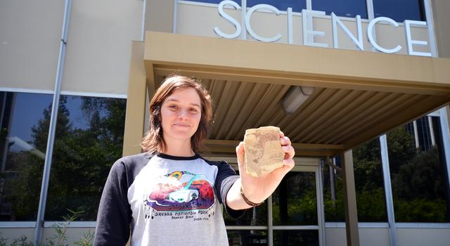 Amanda Allen holds out a rock containing a microfossil in front of the science building at JPL.