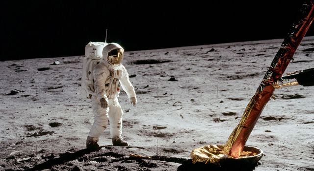 An Apollo 11 astronaut stands on the Moon and one of the legs of the lunar module can be seen in the corner of the image