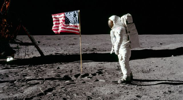 Buzz Aldrin stands on the moon in his puffy, white spacesuit next to an American flag waving in the wind. The command module casts a long, dark shadow nearby.