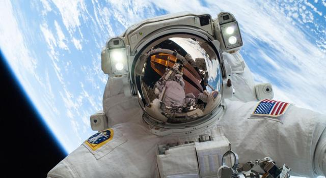 NASA astronaut Mike Hopkins in a spacesuit with the Earth behind him