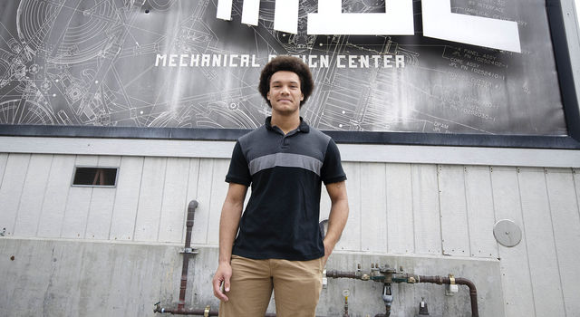 Brandon Ethridge stands in front of a mural made to look like a blueprint on the Mechanical Design Building at JPL.