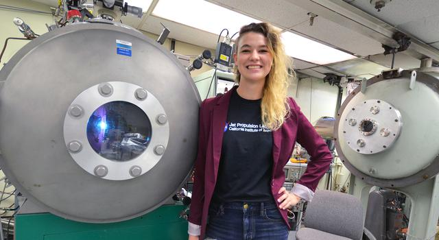 JPL intern Camille Yoke stands in front of a test chamber
