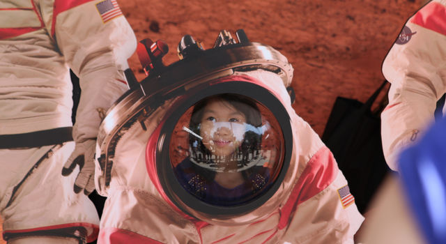 A young visitor at Explore JPL poses with a cutout of an astronaut on Mars.