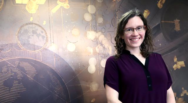 Catherine Elder poses in front of a brown-colored mural of the planets.