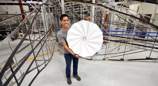 JPL Christopher Esquer-Rosas holds an origami version of the Starshade engineering model behind him.