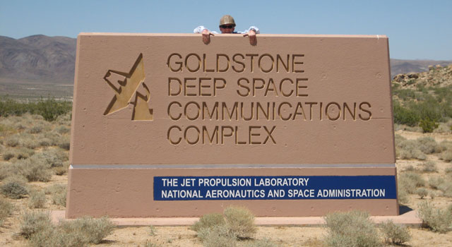 Andrew Crawford looks out over the Goldstone Deep Space Communications Complex sign