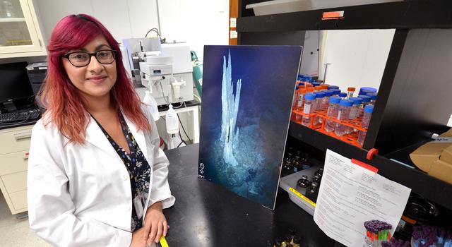 Erika Flores poses for a photo in the lab at JPL