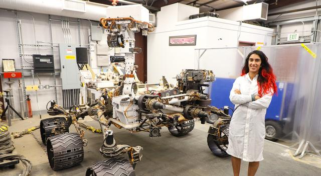 Farah Alibay, wearing a white lab coat, poses for a photo in front of an engineering model of the Curiosity rover