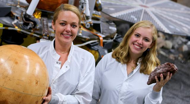 JPL interns Heather Lethcoe and Lauren Berger pose with the InSight engineering model in its testbed at JPL