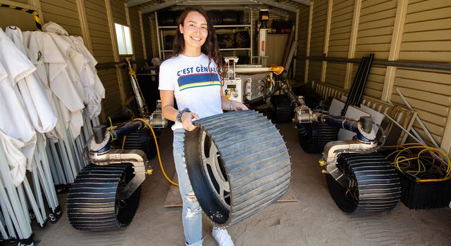 Isabel Rayas holds a spare rover wheel while posing in front of a rover parked in a garage