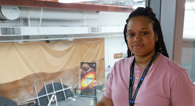Jasmine Cameron poses in the viewing gallery of the In-Situ Instruments Laboratory at JPL