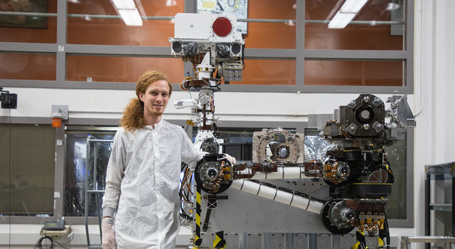 Jeff Carlson stands in an open room posing next to an engineering model of the mast for the Mars 2020 rover
