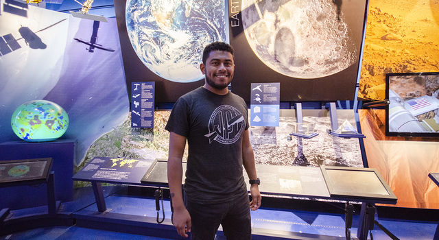 Jose Martinez-Camacho stands in front of a Moon display, featuring a lunar rock sample, in the Visitor Center at JPL.