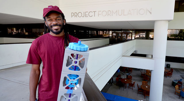 JPL intern Joshua Gaston holds a 3-D printed model of a CubeSat