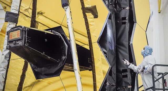 In the cleanroom at Northrop Grumman, a technician inspects the bellows between the hexagonal sections that make up the large honeycomb-shaped mirror on the Webb telescope.