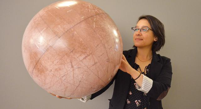 JPL intern Kathy Vega poses with a model of Jupiter's moon Europa