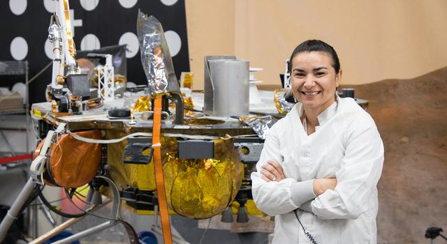 Marleen Sundgaard stands on gravel in a tall room with a test version of the InSight Mars lander behind her.