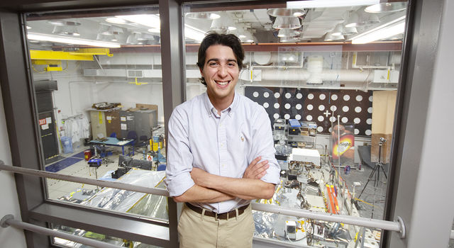 Max Rudolph crosses his arms and smiles at the camera standing in front of a glass window that looks down on the In-Situ Instrument Laboratory