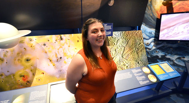 JPL intern Maya Yanez stands in front of the Jupiter display in the lab's museum