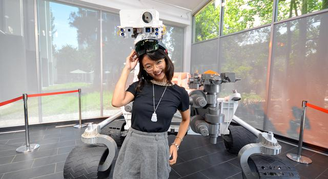 Michelle Vo poses for a photo in front of a full-size model of the Curiosity Mars rover at JPL.