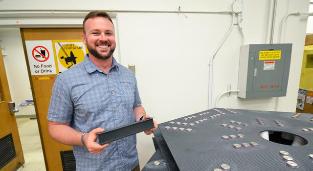 Ryan Loper holds a optical test-bed component he designed during his internship at JPL.