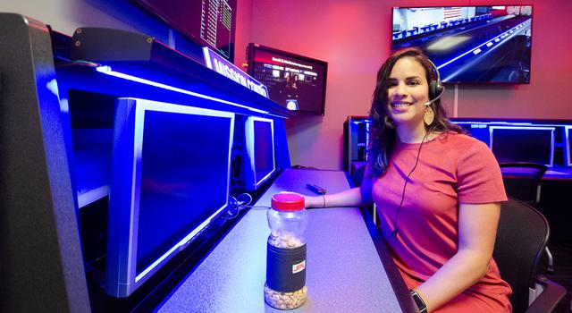 Samalis Santini De Leon poses for a photo with a jar of lucky peanuts in JPL's Space Flight Operations Center.
