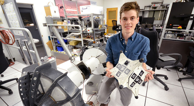 Sawyer Elliott holds a model of a rover like the one he's developing at JPL