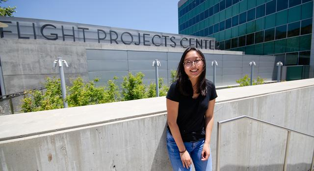 "Tiffany Shi poses for a photo in front of a steel and glass building at JPL with the words ""Flight Projects Center"" displayed on the front of the building."