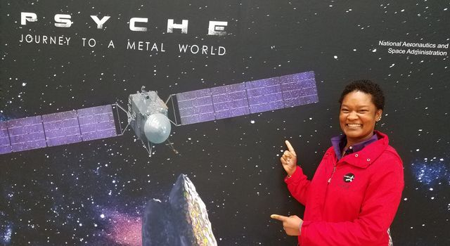 Tracy Drain poses in front of a Psyche mission backdrop