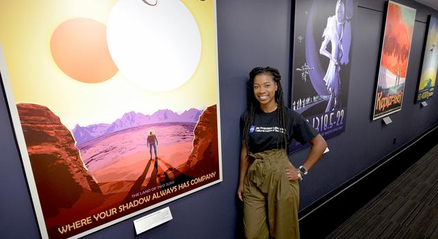 "JPL intern Tre'Shunda James stands in front of NASA's ""Visions of the Future"" posters"