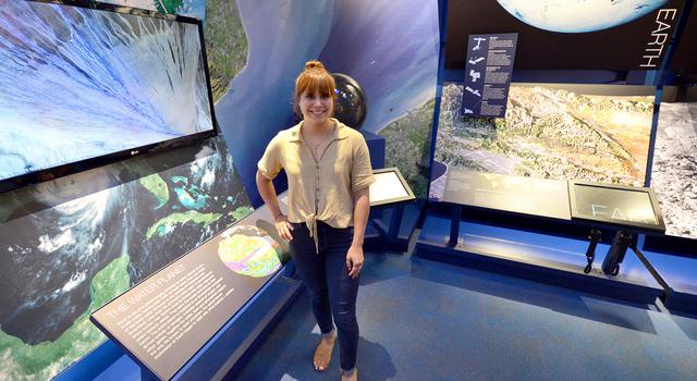 Vicky Espinoza stands in front of an Earth science display at JPL