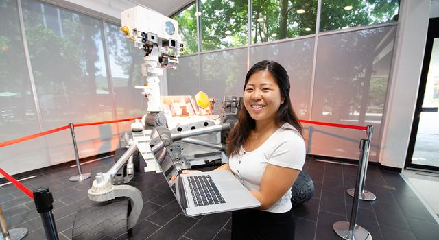 Vivian Li holds a computer and poses for a photo in front of a full-size model of the Mars rover Curiosity.