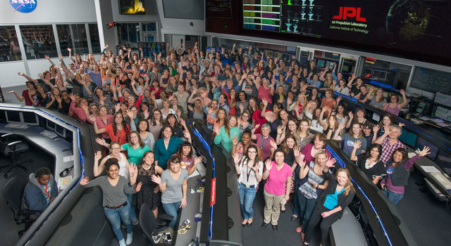 Women working in STEM at NASA's Jet Propulsion Laboratory pose for a photo in mission control in honor of Women in Science Day.