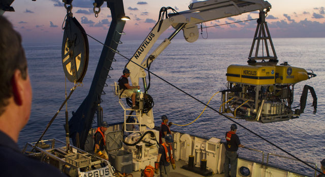 A man watches as a crane lowers an ROV into the ocean from the E/V Nautilus research vessel at sunset