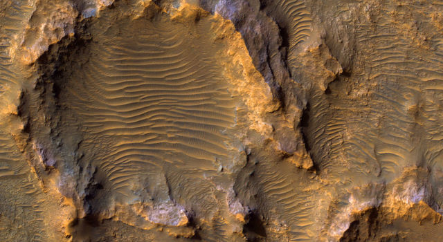 Dunes stretch out across the center of a jagged, rocky crater shown in tan in orange with spots of blue and purple.